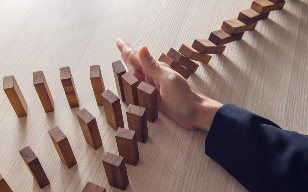 risk management compliance program-hand-dominos